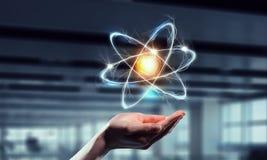 Atomsymbolen gömma i handflatan in Blandat massmedia Blandat massmedia arkivfoto