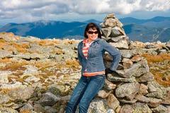 Atop Mount Washington. Beautiful woman sitting on a Stone marker atop Mount Washington Royalty Free Stock Image