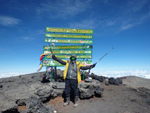 Atop Mt. Kilimanjaro. A climber celebrates reaching the top of Mt. Kilimanjaro, Tanzania, Africa Stock Photos