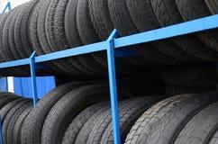 Atormente con la variedad de neumáticos de coche en tienda del automóvil Mucho t negro imagenes de archivo