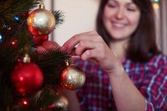 Atormente el tiro en la muchacha contenta que adorna el árbol imperecedero con las bolas Fotos de archivo