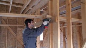 Atornillar el tornillo en un tablero de madera El trabajador en el especialista a la ropa fija a tableros un tornillo y el arma d almacen de video
