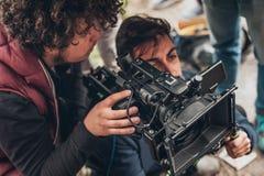 Atrás da cena Filme do tiro do operador cinematográfico e do assistente com came fotografia de stock royalty free
