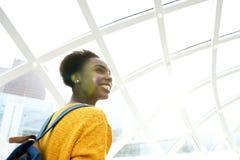 Atrás da jovem mulher feliz na estação com trouxa foto de stock