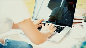 Atrás da jovem mulher que datilografa no teclado do portátil e no crédito c do uso Foto de Stock
