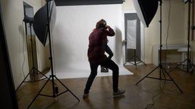 Atrás da sessão da sessão fotográfica das cenas de um modelo magro encaracolado louro para um tipo famoso da roupa em um estúdio  filme