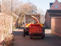 atrás da vista do caminhão com a máquina vermelha da retalhadora atrás da rua Fotografia de Stock Royalty Free