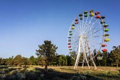 Atração abandonada - uma roda de Ferris com as cabines coloridas na floresta do russo Imagem de Stock Royalty Free