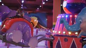 Atração das crianças Equitação da menina em um carrossel do elefante da criança no parque de jogo no centro da alameda filme