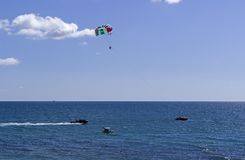 Atracción del agua - un barco remolca a hombres en un paracaídas sobre el mar Fotografía de archivo