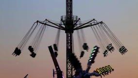 Atracciones del parque de atracciones en la puesta del sol (07) almacen de video