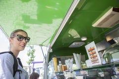 年轻atractive在绿色食物卡车的妇女预定的膳食 库存图片