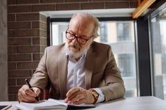 Atractive a éprouvé le vieil homme écrivant l'information importante dans le bloc-notes Images stock