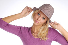 Atractive blonde woman with hat in violet sweater Stock Images