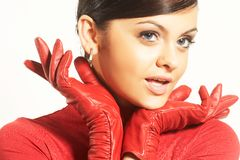 Atractive brunet in red blouse and red gloves Stock Photography