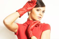Atractive brunet in red blouse and red gloves Royalty Free Stock Photo