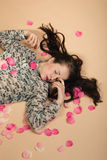 Atractive brunette girl lying on beige background Royalty Free Stock Photos
