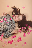 Atractive brunette girl lying on beige background Royalty Free Stock Images