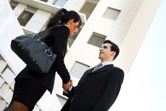 Businessman and businesswoman shaking hands outside of office bu Stock Images