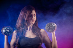 Atractive fit woman works out with dumbbells as a fitness concep Stock Photography