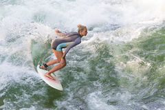 Atractive garten den sportiga flickan som surfar på berömd konstgjord flodvåg i Englischer, Munich, Tyskland Arkivfoton