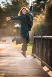 Atractive Gelukkige Vrouw die omhoog door een Houten Oude Brug in F springen stock foto's