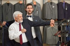 Atractive guy and older grey man in costumes in male store. royalty free stock image