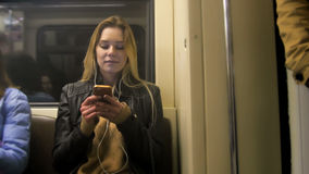 Atractive happy girl with long blonde hair in leather jacket  straightens  use gadget in metro Stock Photography