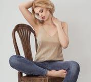 Atractive kobieta w złocistym koszulowym obsiadaniu na brown krześle Fotografia Royalty Free