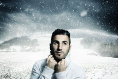 Atractive man warm up with pullover. And looking sideways to fallen snowflakes in front of winter landscape Stock Images