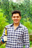 Atractive man wearing casual clothes holding a hammer in a forest background Royalty Free Stock Photography