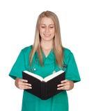 Atractive medicinsk flicka som läser en bok Arkivbilder