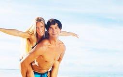 Atractive par som har gyckel på stranden Arkivfoto
