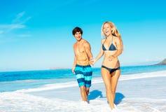 Atractive par som har gyckel på stranden Royaltyfria Bilder