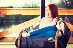 Atractive red-haired woman resting sitting on Rocking chair in f Royalty Free Stock Photo
