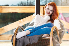 Atractive red-haired woman resting sitting on Rocking chair in front of window Royalty Free Stock Photos