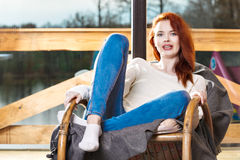 Atractive red-haired woman resting sitting on Rocking chair in front of window Royalty Free Stock Photography
