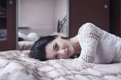Girl lying on the bed Stock Photography