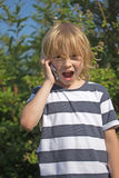 Atractive surpriced blond boy is calling Royalty Free Stock Photo