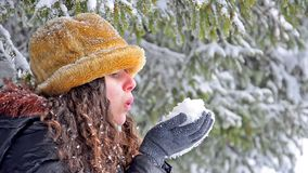 Atractive teen in hat blowing snowflakes Royalty Free Stock Image