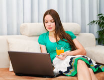 Atractive woman working on her laptop. Attractive woman working on laptop with orange juice in her hand Royalty Free Stock Images