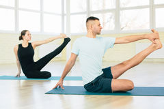 Atractive yoga couple , man and woman, practice exercises in a training hall Stock Photography