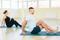 Atractive yoga couple. Men and woman, practice exercises in a training hall background. Yoga concept Royalty Free Stock Photography