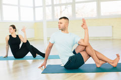 Atractive yoga couple. Men and woman, practice exercises in a training hall background. Yoga concept Stock Image