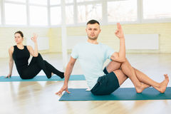 Atractive yoga couple. Men and woman, practice exercises in a training hall background. Yoga concept Royalty Free Stock Image