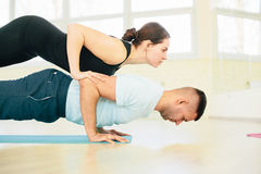 Atractive yoga couple. Men and woman, practice exercises in a training hall background. Yoga concept Royalty Free Stock Images