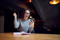 Atractive young girl trying understand bussines strategy of hostel and restraunt. Happy female freelancer celebrating important victory in company from internet Royalty Free Stock Image