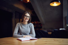 Atractive young girl trying understand bussines strategy of hostel and restraunt. Portrait of pretty smart correspondent sitting indoors at wooden table with Royalty Free Stock Image