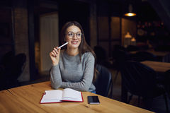Atractive young girl trying understand bussines strategy of hostel and restraunt. Sitting at wooden table working on writing new article caffee shop and Stock Images