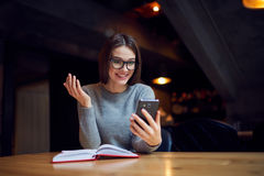Atractive young girl trying understand bussines strategy of hostel and restraunt. Smiling pretty business woman in eyeglasses reading positive news on smartphone Stock Photos